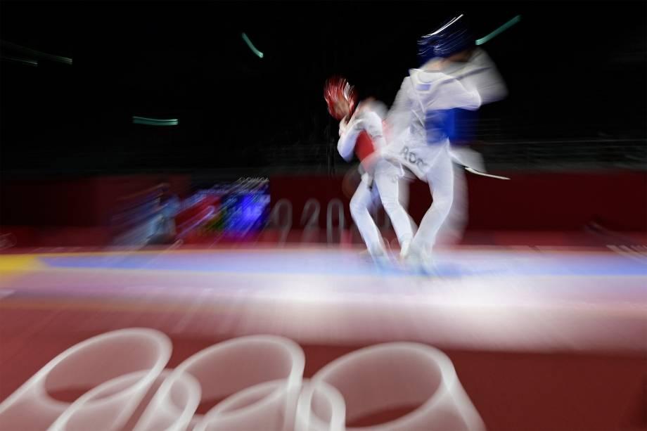 O russo Vladislav Larin (azul) e Pita Taufatofua, de Tonga, lutam em eliminatória do taekwondo -