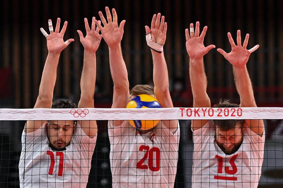 Os poloneses Fabian Drzyzga, Mateusz Bieniek e Michal Kubiak durante tentativa de bloqueio em partida contra a Venezuela no vôlei -