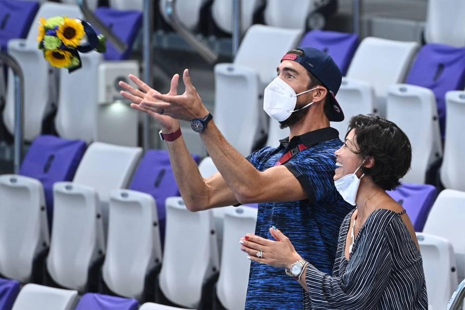 Michael  Phelps, ex-nadador dos EUA, pega um buquê de flores enquanto assiste a premiação do revezamento 4x200m livre feminino -