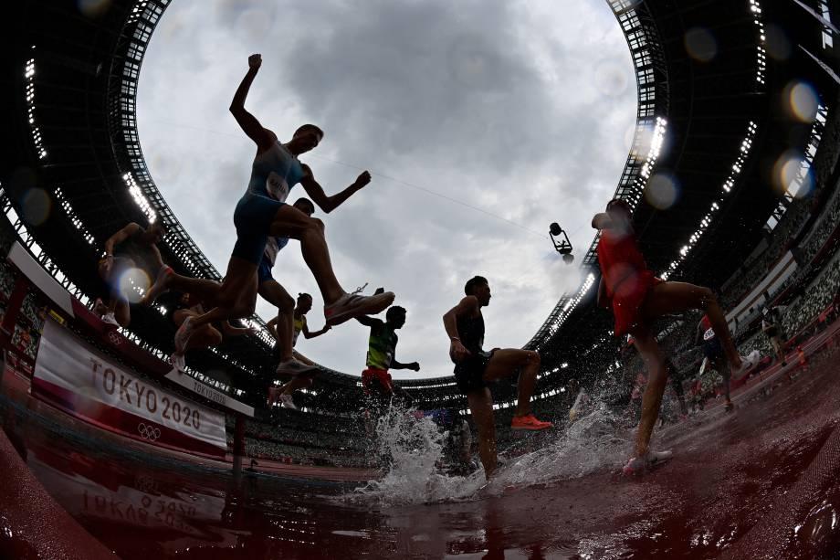 Atletas durante as eliminatórias da prova de 3000m com obstáculos no atletismo -