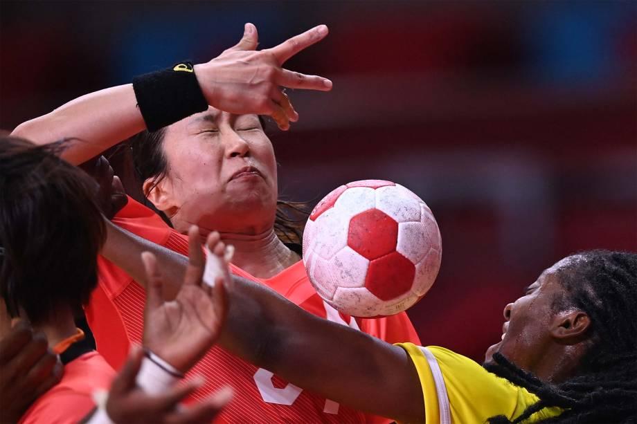 Jogadoras de Japão e Angola durante disputa pela bola em partida no handebol -