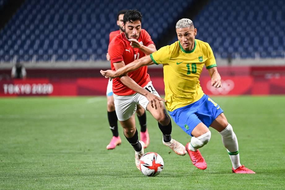 O meio-campista egípcio Akram Tawfik em disputa de bola com o atacante brasileiro Richarlison -