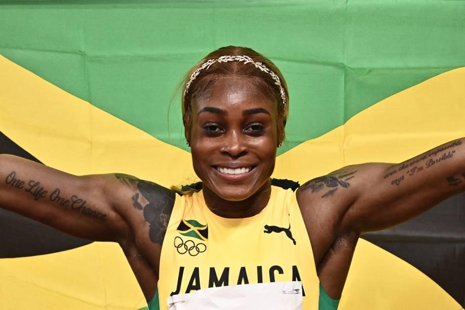 A atleta Elaine Thompson-Herah posando com a bandeira jamaicana -