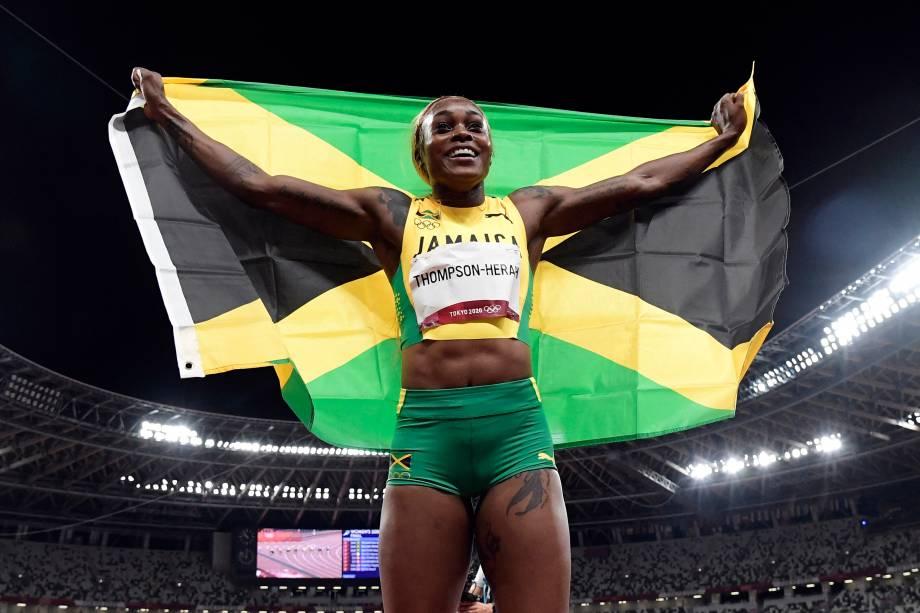 A atleta Elaine Thompson-Herah comemorando com a bandeira da Jamaica -