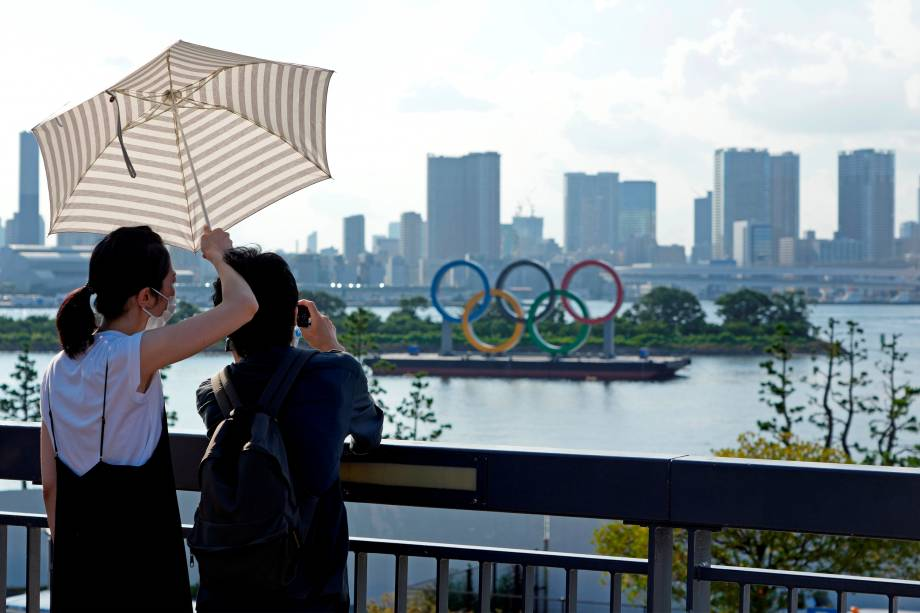 Mulher protege-se do sol enquanto fotografa os anéis olímpicos em Tóquio -