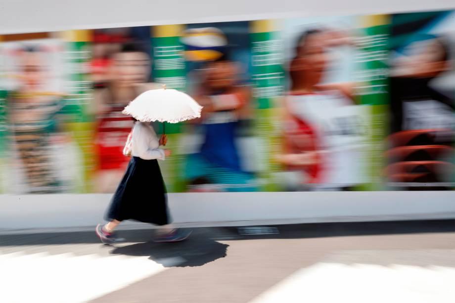 Pedestre proteje-se do sol ao passar em frente a campanha publicitária dos Jogos Olímpicos -