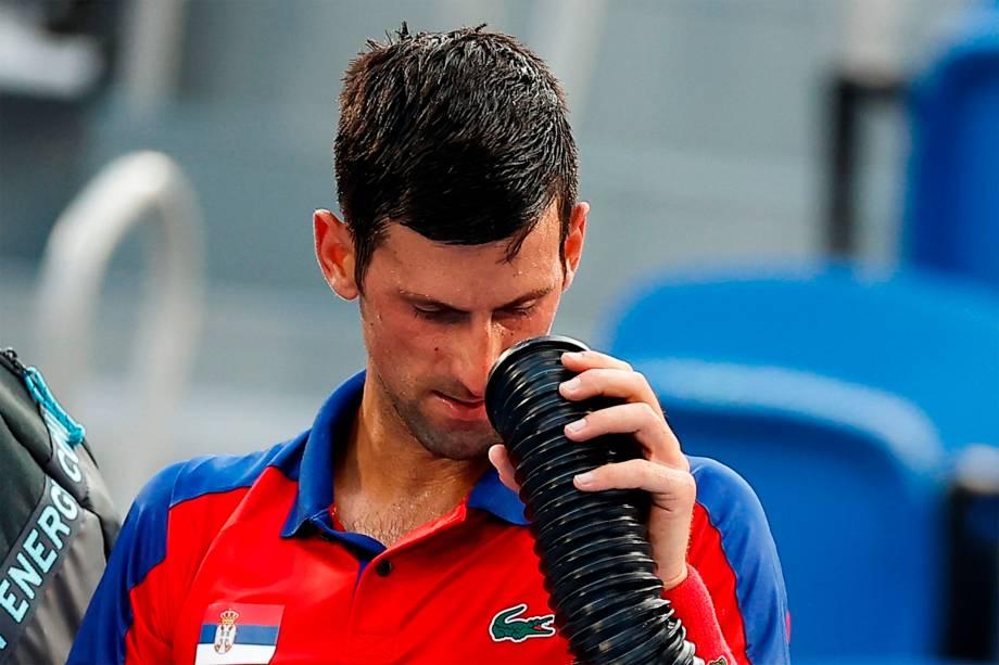 O sérvio Novak Djokovic refresca-se em partida de tênis -