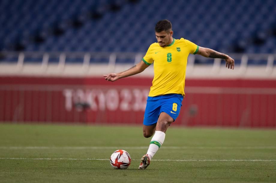 Bruno Guimarães durante lançamento de bola na partida -