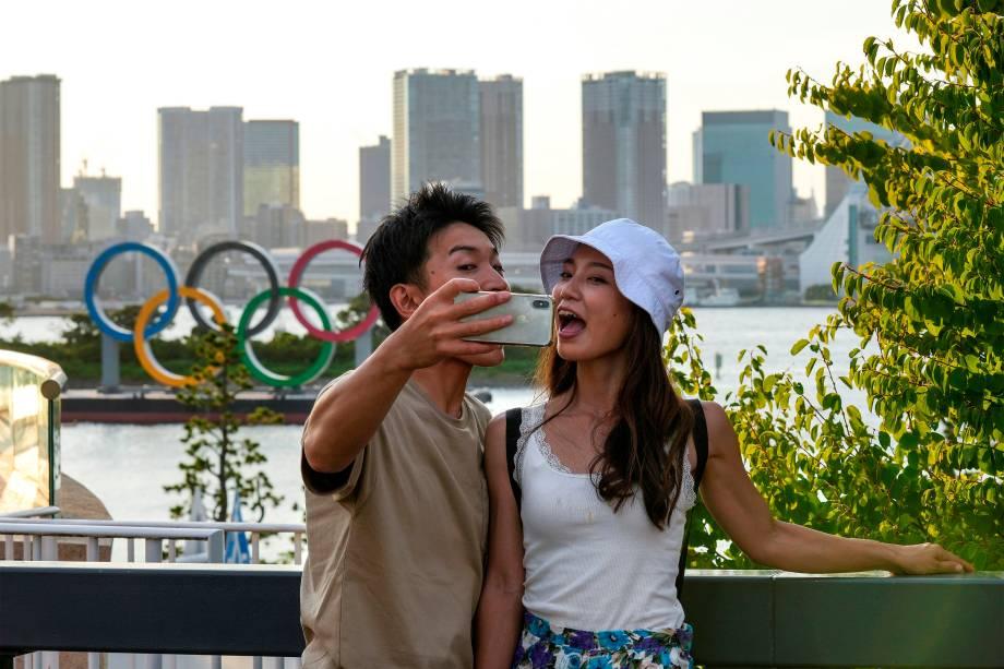 Casal faz selfie em frente aos anéis Olímpicos em Odaiba durante as Olimpíadas de Tóquio -