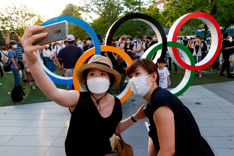 Mulheres fazem selfie em frente aos anéis Olímpicos durante a cerimônia de abertura das Olimpíadas 2020, em Tóquio -