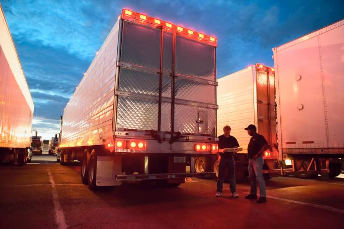 Two truck drives checking dispatch papers while standing next to truck trailers in a large parking lot at night.