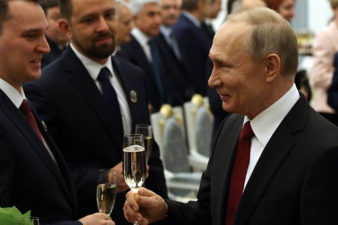 Russian President Vladimir Putin (R) toasts with Doctor of physics and mathematics Sergei Makarov (L)