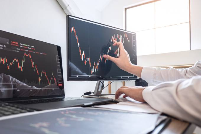 Cropped Hands Of Businesswoman Analyzing Stock Market Data Over Computer In Office