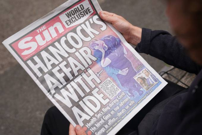 A person reads a copy of the Sun newspaper in Westminster, London, with the story and pictures of Health Secretary Matt Hancock appearing to kiss his adviser Gina Coladangelo