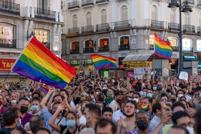 Demonstrators chant slogans and raise rainbow flags during