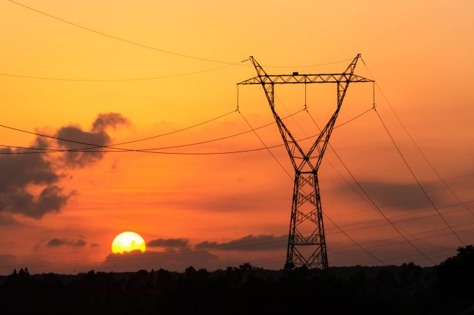 Electricity transmission tower with sunset in the background.