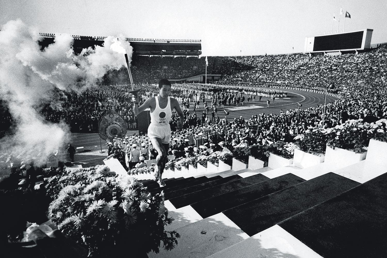 1964 -O sobrevivente de Hiroshima a caminho da pira no estádio lotado: recuperação após a II Guerra -