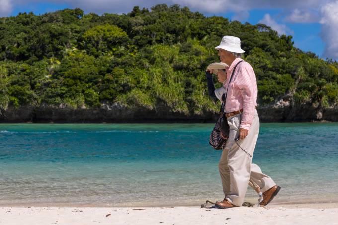Old japanese couple walking along the tropical lagoon with clear blue water in Kabira bay, Yaeyama Islands, Ishigaki, Japan