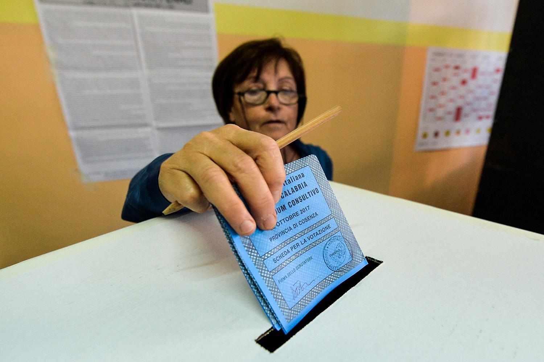 Nella foto, una donna mette la scheda elettorale nell'urna durante il referendum -