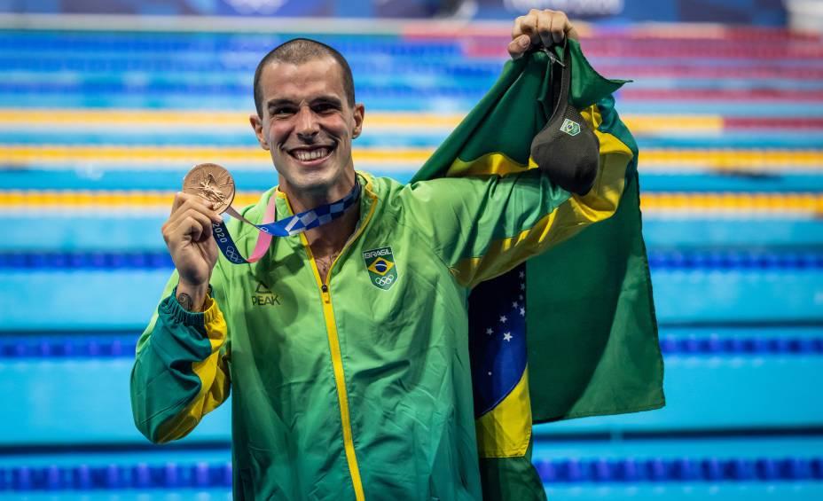 Fratus posando com a medalha de bronze e a bandeira do Brasil -
