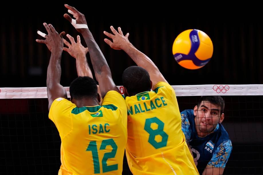 Os brasileiros Isac e Wallace tentam bloquear o argentino Ezequiel Palacios durante partida entre as seleções -