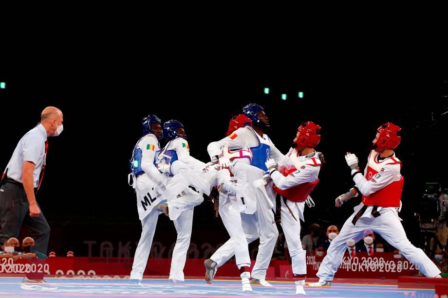 Seydou Fofana (azul), de Mali, e Ulugbek Rashitov (vermelho), do Uzbequistão, em prova do taekwondo masculino -