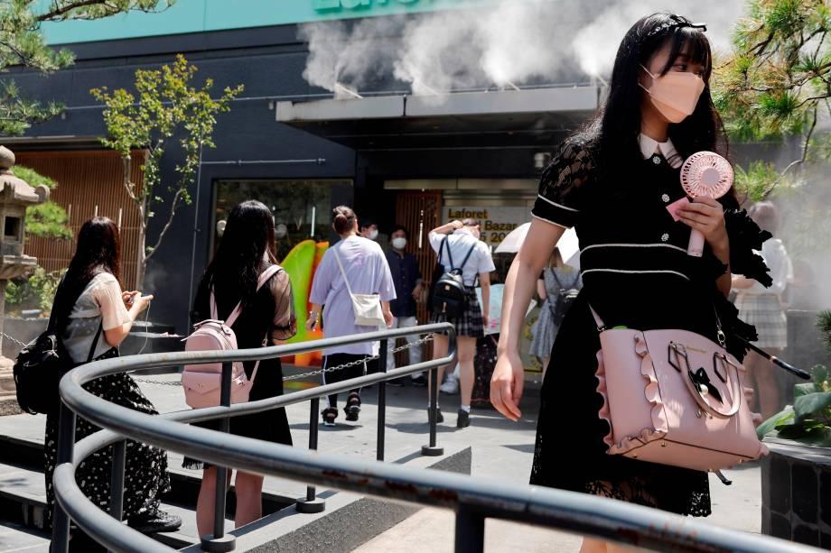 Mulher carrega ventilador portátil devido ao calor em Harajuku, Tóquio -