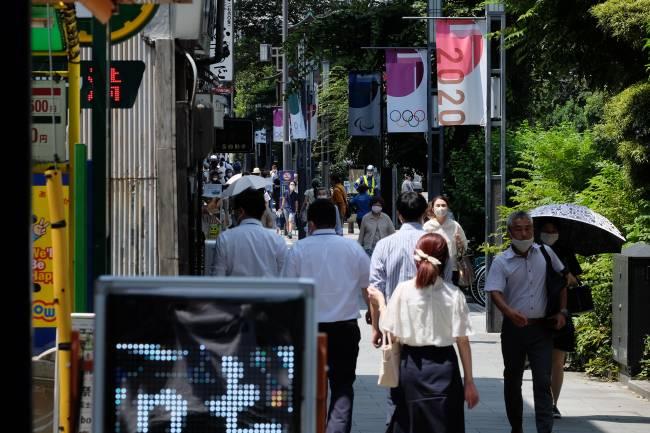 Transeuntes andam por rua decorada com banners dos Jogos, no centro de Tóquio (Carlos Kato)