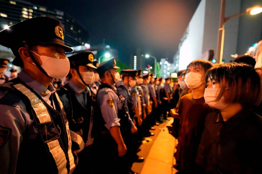 Policiais bloqueiam manifestantes que protestam contra os Jogos Olímpicos 2020 em frente ao Estádio Olímpico, em Tóquio -