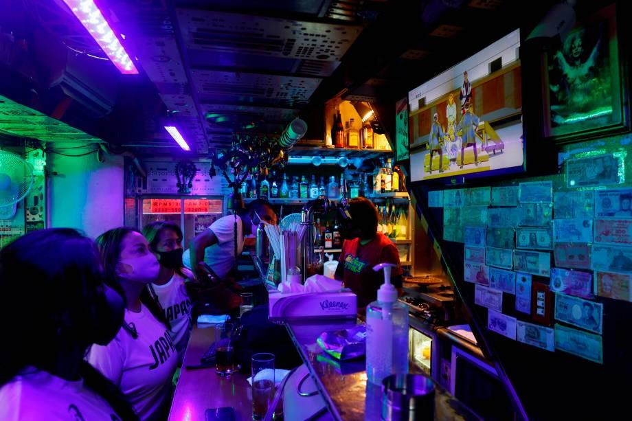 Clientes de um bar acompanham pela televisão a cerimônia de abertura dos Jogos Olímpicos de Tóquio -