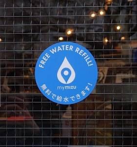 Adesivo do programa mymizu em porta de um café em Tóquio que sinaliza um ponto de abastecimento de garrafinhas d'água