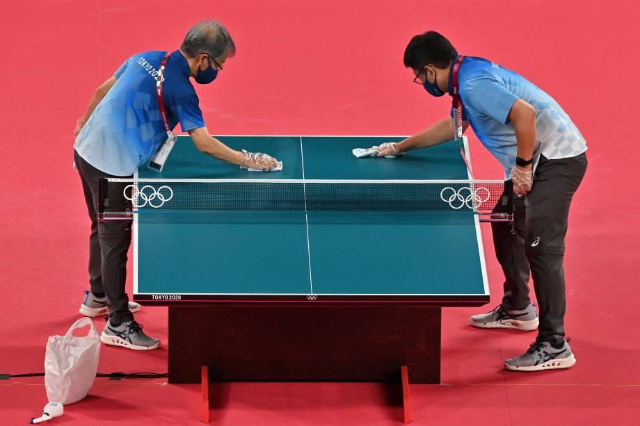 Voluntários fazem limpeza durante os treinos das equipes de tênis de mesa no Tokyo Metropolitan Gymnasium -