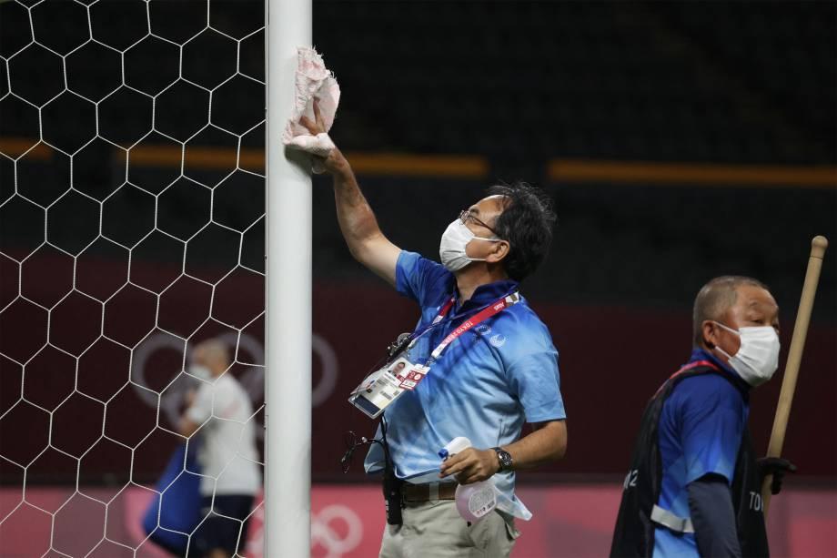 Voluntário desinfeta gol no Estádio Sapporo Dome após a partida entre Egito e Espanha -