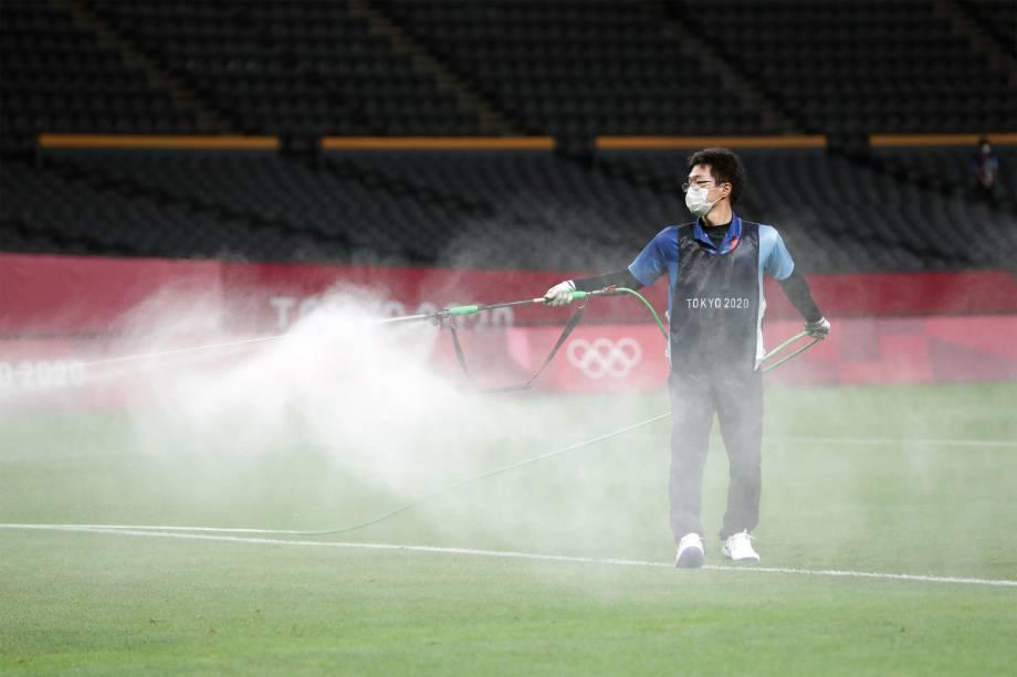 Voluntário desinfeta o Estádio Sapporo Dome antes de partida de futebol entre Argentina e Austrália -