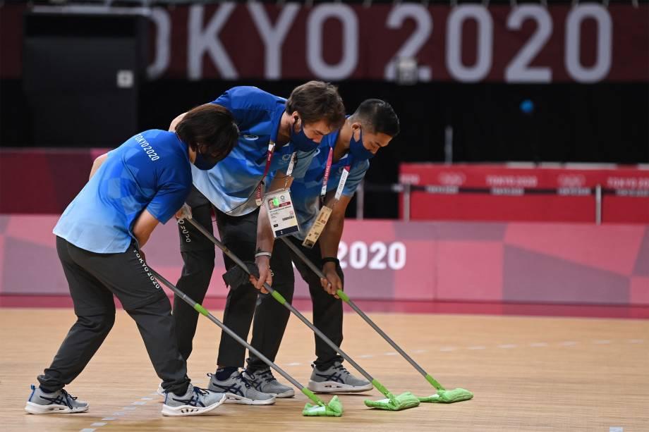 Voluntários limpam o chão durante a partida de handebol feminino entre Brasil e Rússia -