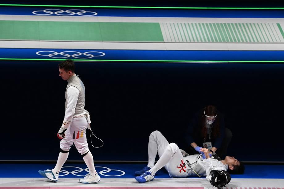 Cheung Siu Lun, de Hong Kong, recebe atendimento médico na luta contra o alemão Andre Sanita -