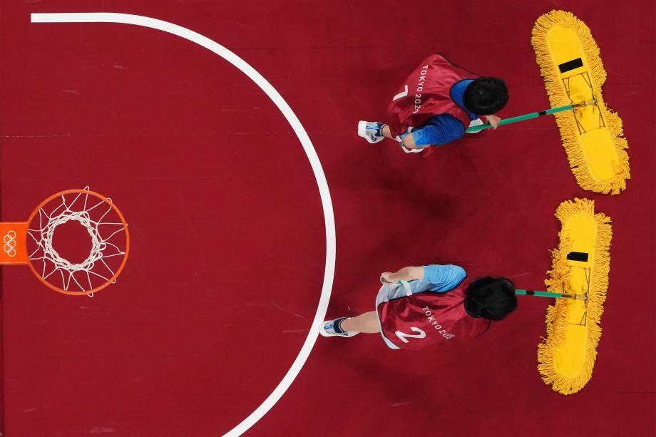 Voluntários secam a quadra durante a partida de basquete feminino entre França e Japão -