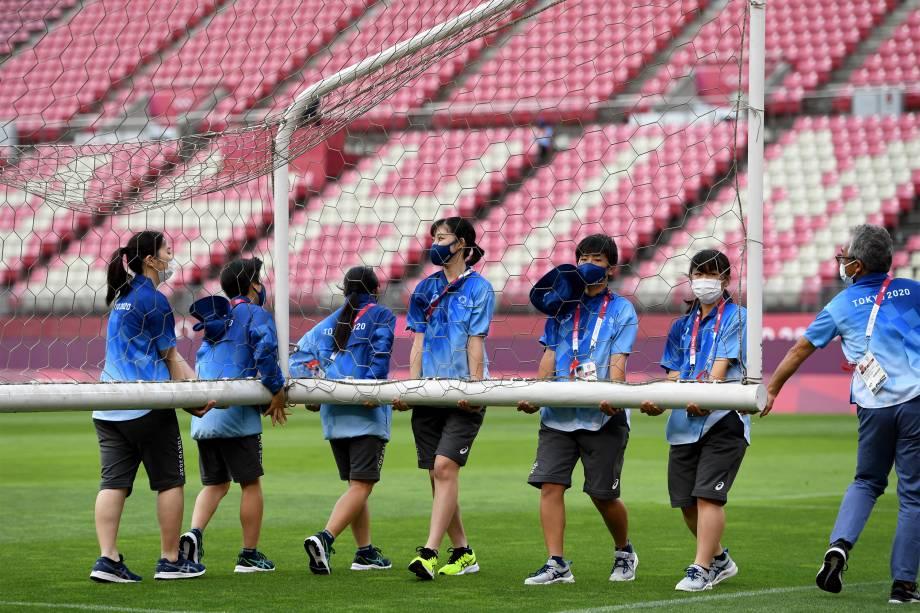 Voluntários carregam gol antes da partida de futebol feminino entre Estados Unidos e Austrália -