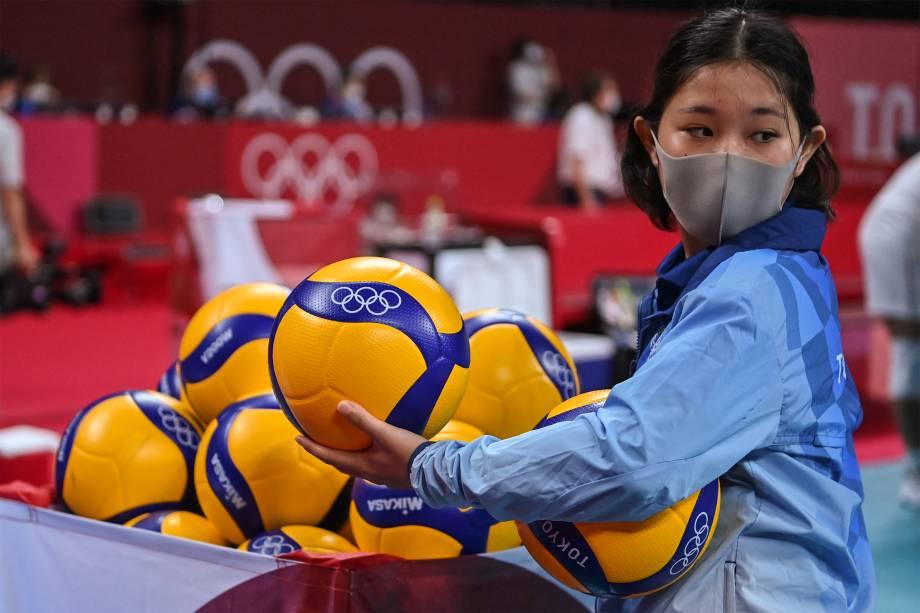 Voluntária organiza bolas antes da partida de vôlei masculino entre Canadá e Irã -
