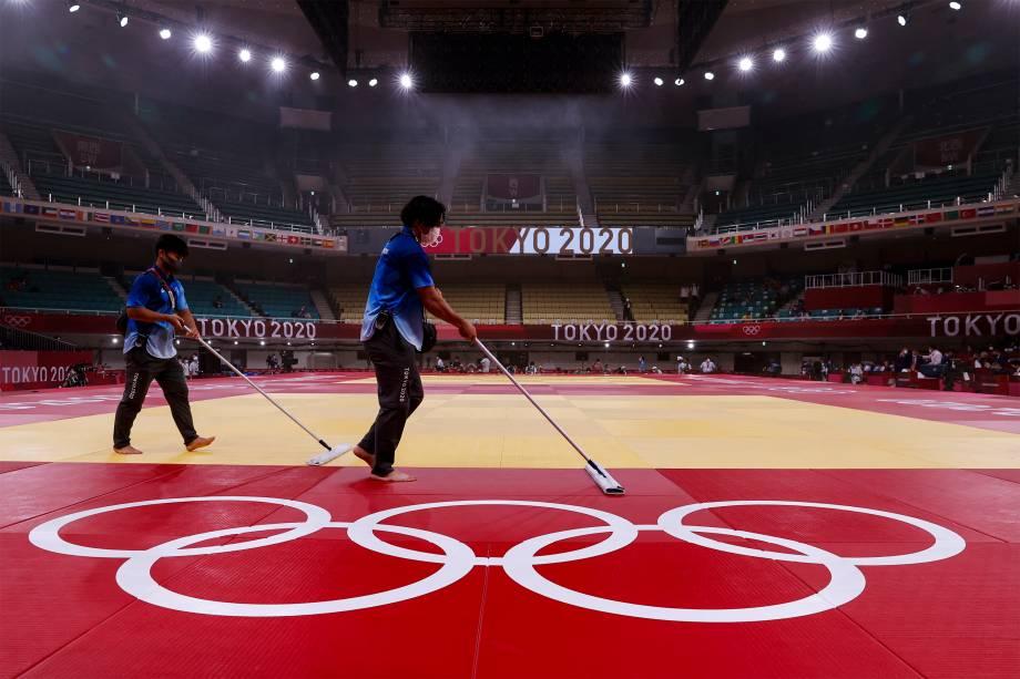Voluntários desinfetam o piso para o quinto dia de competições do judô -