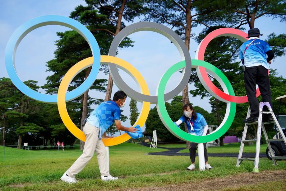 Voluntários limpam os anéis Olímpicos no Kasumigaseki Country Club -