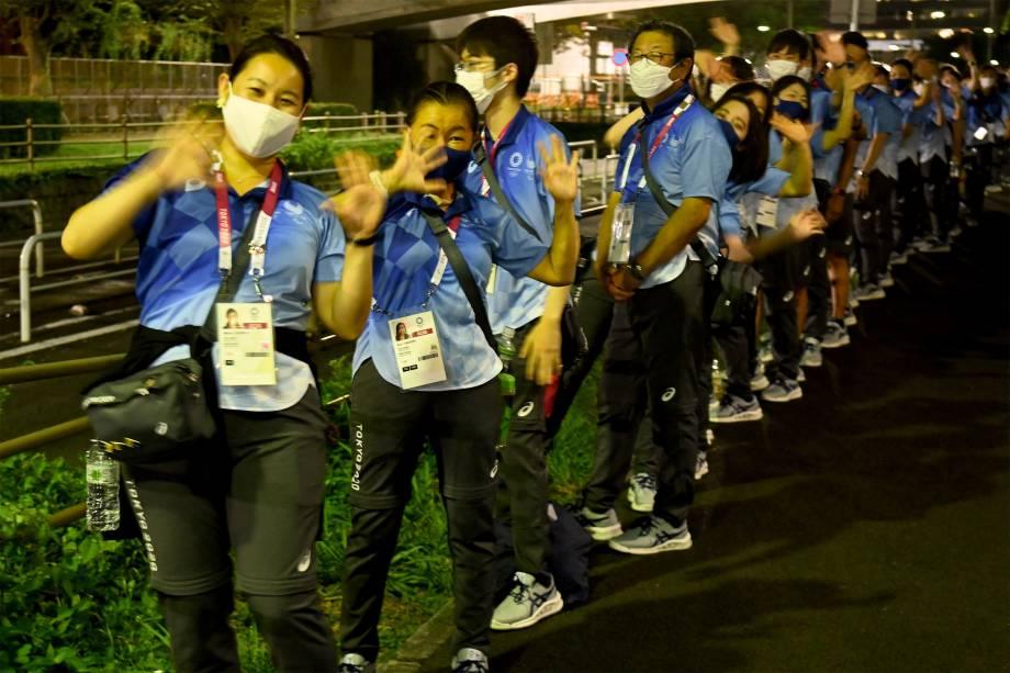 Voluntários japoneses em frente ao Tokyo Aquatics Centre -