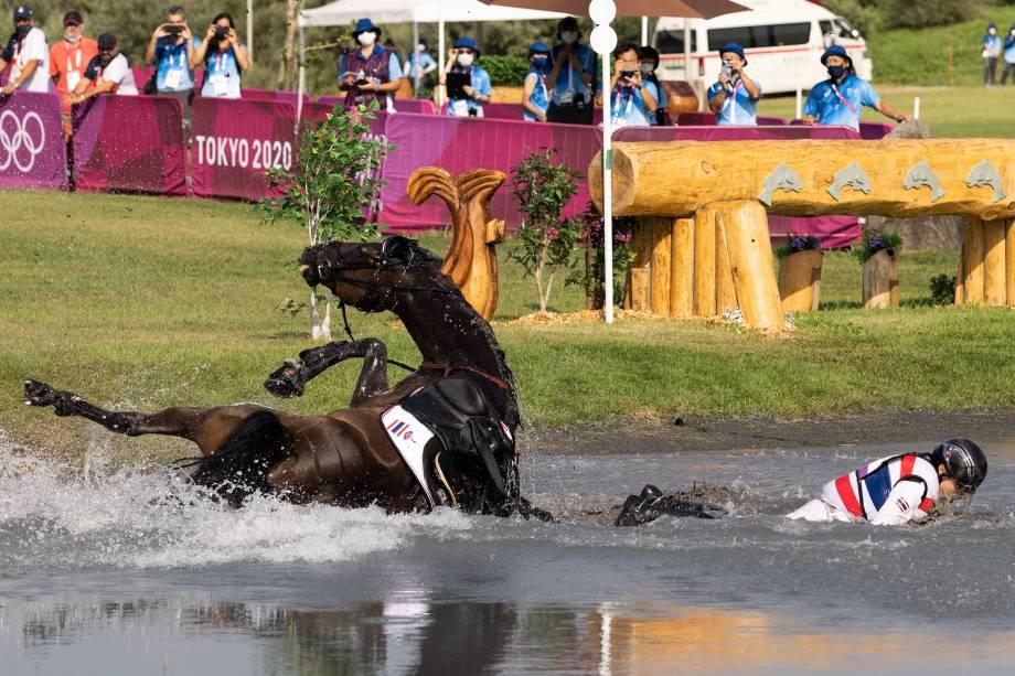 O tailandês Arinadtha Chavatanont cai com o seu cavalo na água durante prova -