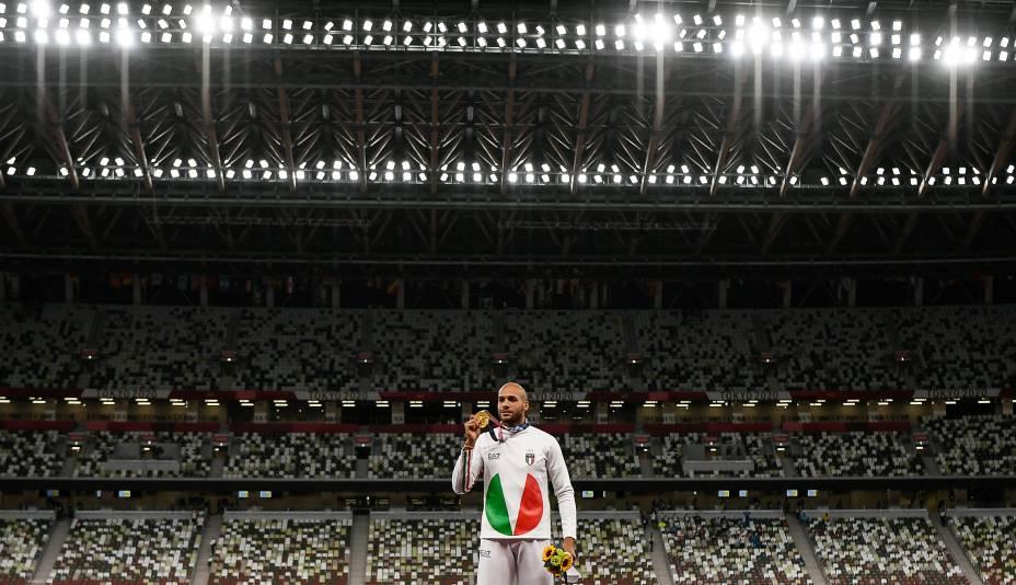 O italiano Lamont Marcell Jacobs posa para foto no pódio com a medalha de ouro conquistada na prova de 100m no atletismo -