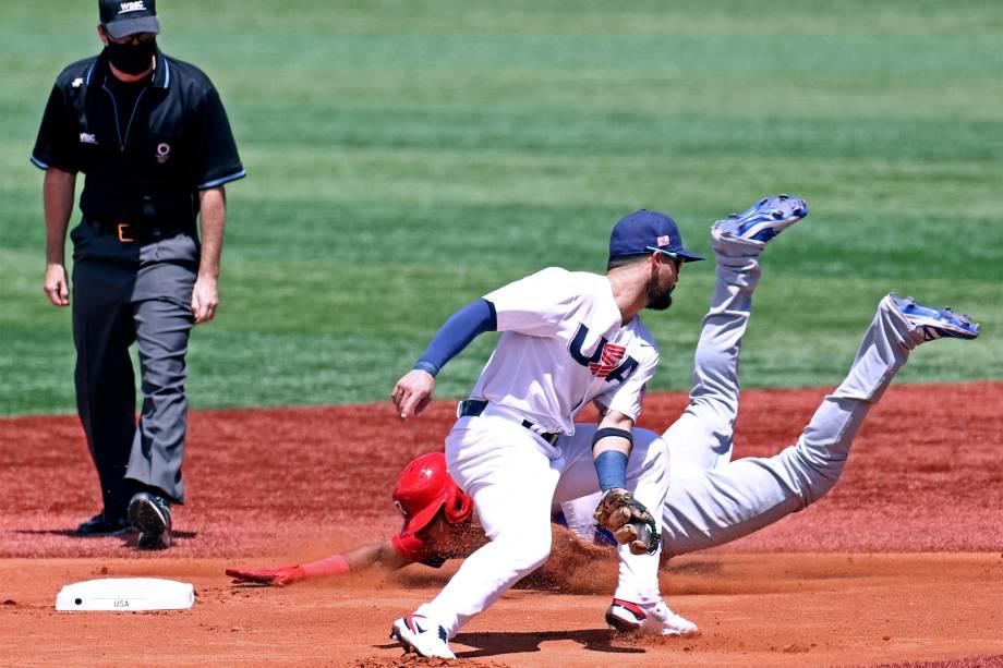 Erick Mejia, da República Dominicana, mergulha na segunda base enquanto o americano Eduardo Alvarez pega bola em partida de beisebol -