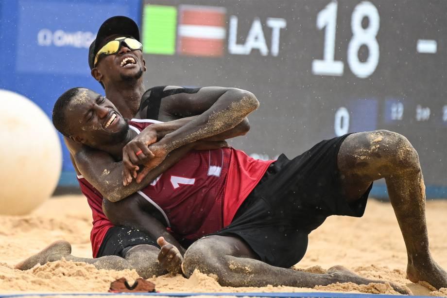 Ahmed Tijan (atrás) e Cherif Younousse , do Qatar, comemoram ao ganhar o bronze na partida e vôlei de praia contra a Letônia -