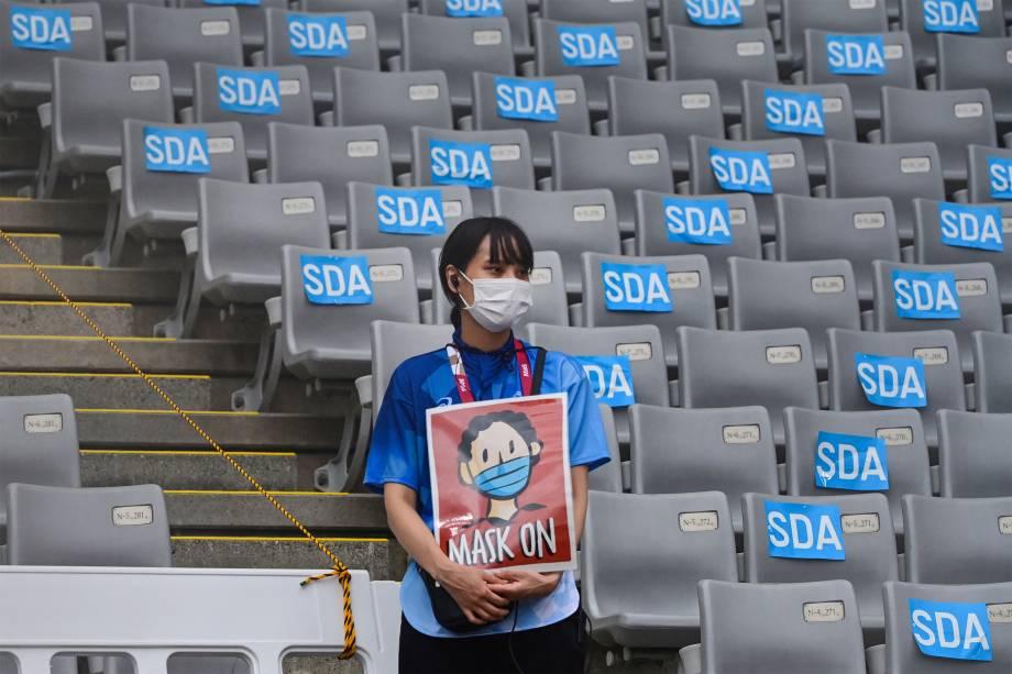 Voluntária segura cartaz pedindo o uso de máscaras antes da competição de pentatlo -