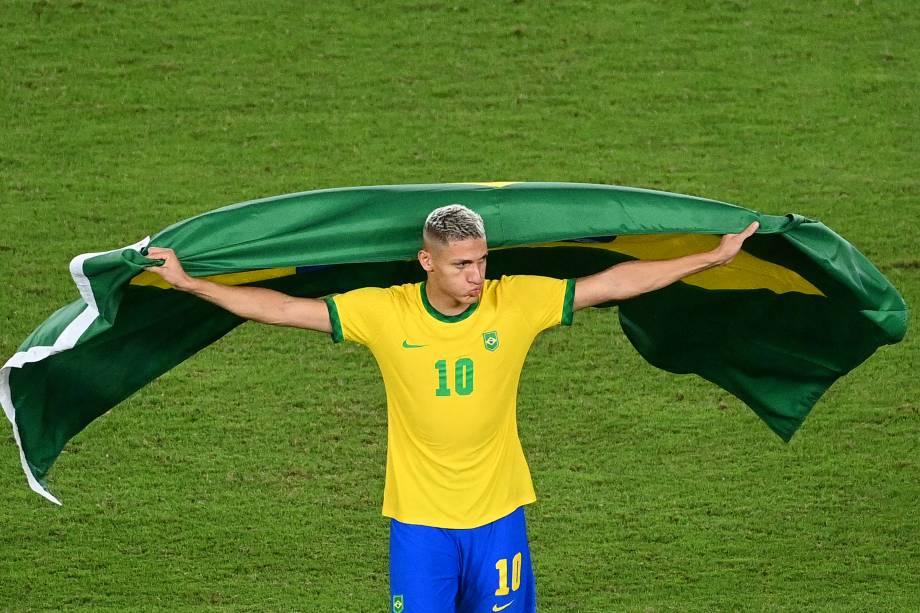 Richarlison comemorando a o título com uma bandeira do Brasil -