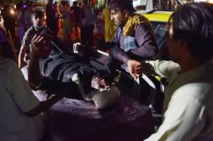 Equipe médica socorre homem machucado após explosão nos arredores do aeroporto de Cabul, no Afeganistão