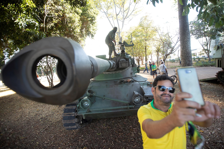 BRA121. BRASÍLIA (BRASIL), 10/08/2021. - Simpatizantes del presidente de Brasil, Jair Bolsonaro, se toman fotografías junto a los tanques estacionados en la Esplanada do Ministerios, este martes en la ciudad de Brasilia. El presidente de Brasil, Jair Bolsonaro, recibió este martes un inusual desfile militar en Brasilia, un despliegue que fue visto por la oposición como un intento de líder de la ultraderecha brasileña por intimidar al Congreso durante una votación clave para el Gobierno. EFE/ Joédson Alves